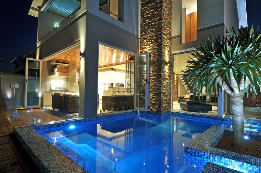 night view over pool to double storey custom home in hillarys.