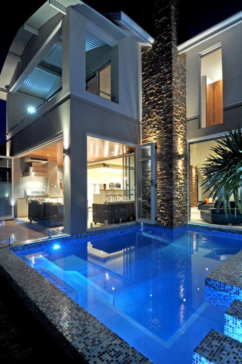 portrait night view over swimming pool taking in two storey home.