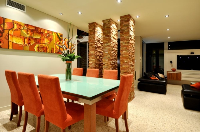 bright dining area next to rough stone columns.